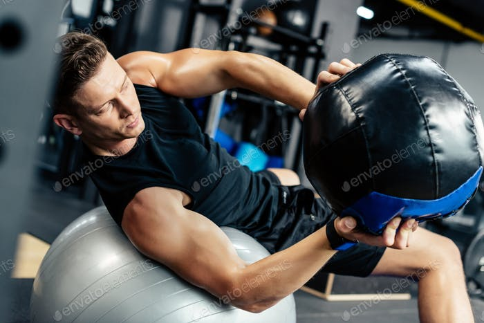 young muscular sportsman training on fitness ball with medicine ball in gym