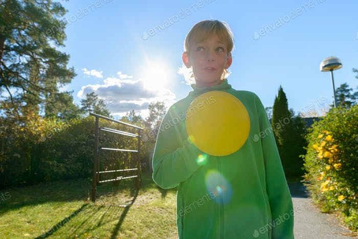 Young handsome boy thinking while holding Frisbee in the front yard