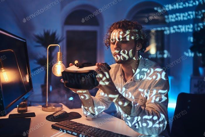 Nachdenklicher Typ hält Virtual-Reality-Headset und sieht es im dunklen Raum an