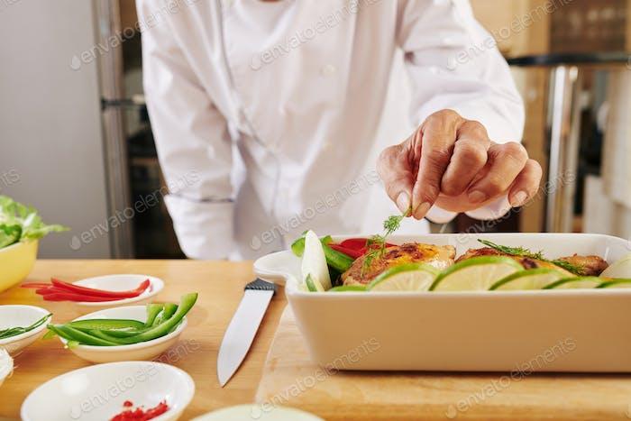Chef garnishing baked chicken