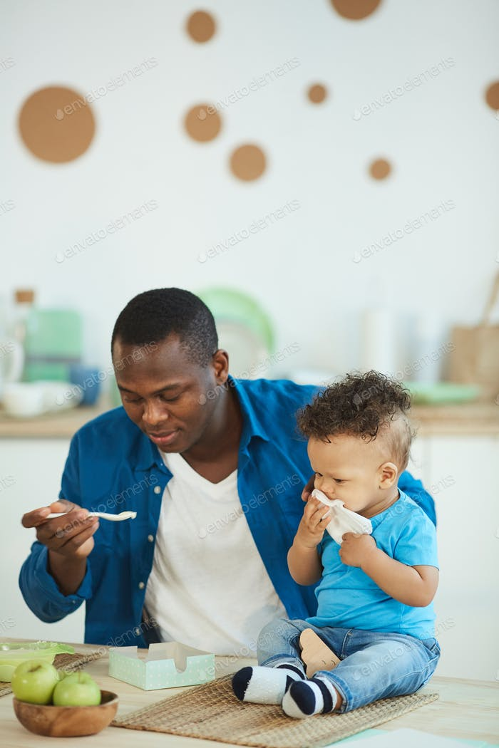 Caring Father Feeding Baby Son