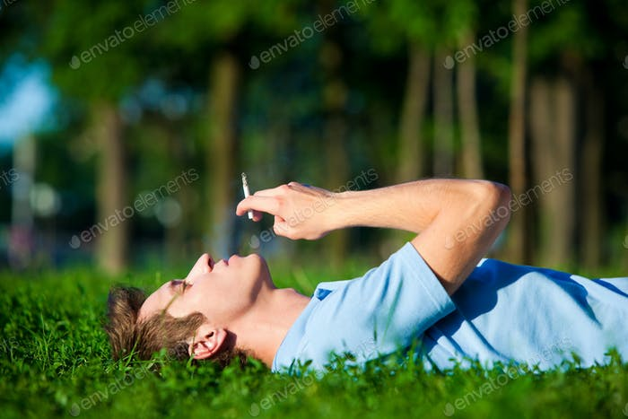 Young man lying on green grass and enjoying smoking