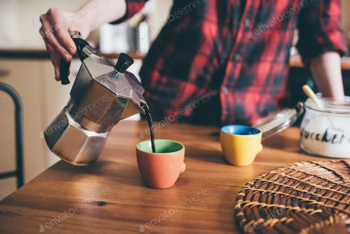 Close up of the hand of young woman pouring coffee