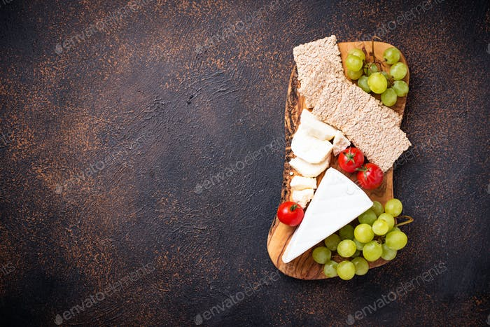 Cheese plate with brie, grape and wine