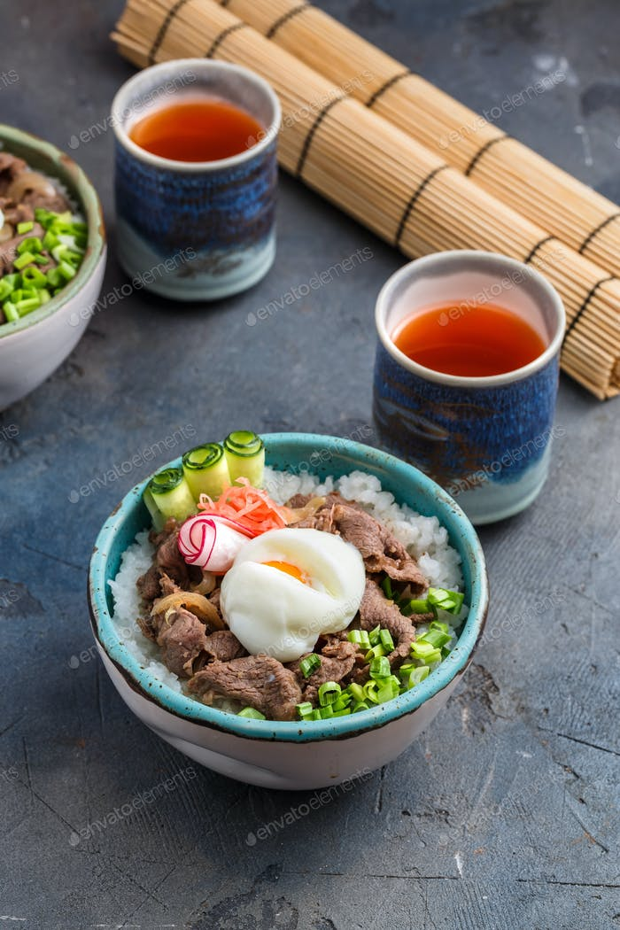 Rice and beef bowls with tea, concrete background