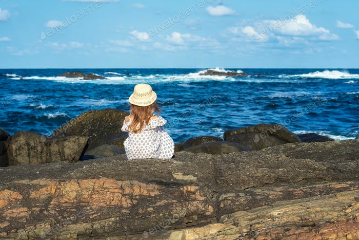 Girl at a rocky coastline