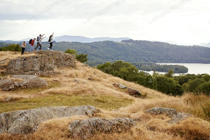 A group of five mixed race young adult friends arrive at summit with arms in the air