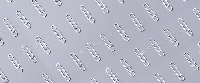 Pattern of white paper clips on grey background. Back to school. Office, business, paperwork