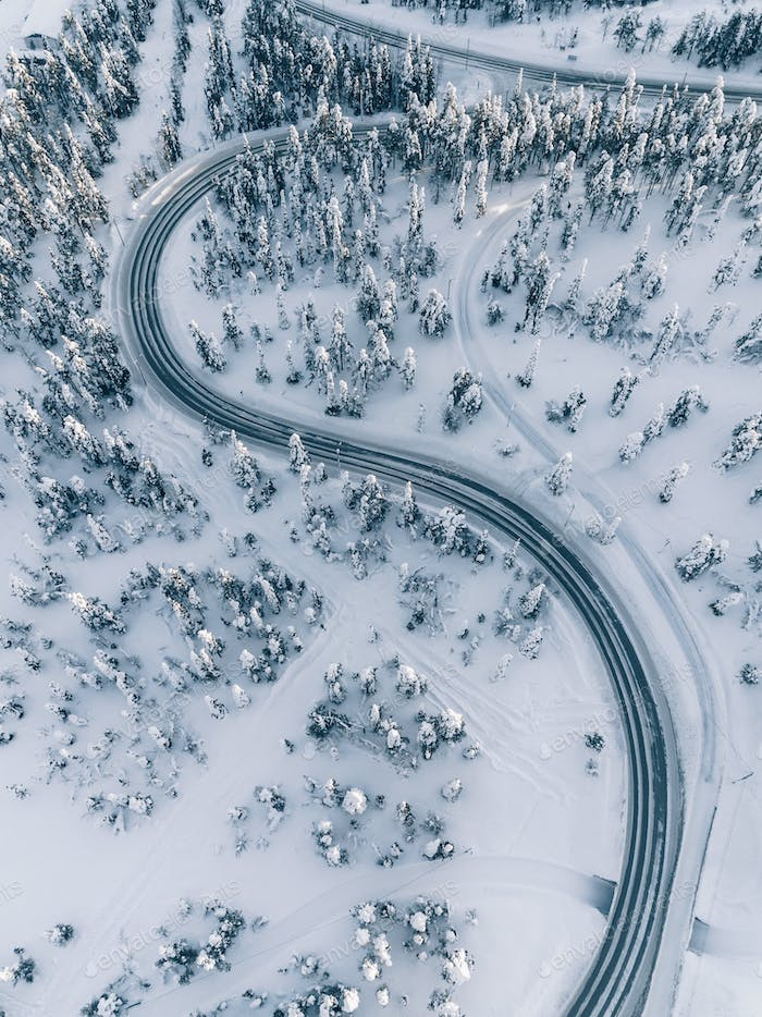 Aerial view of winter road in the forest covered with snow, Finland Lapland