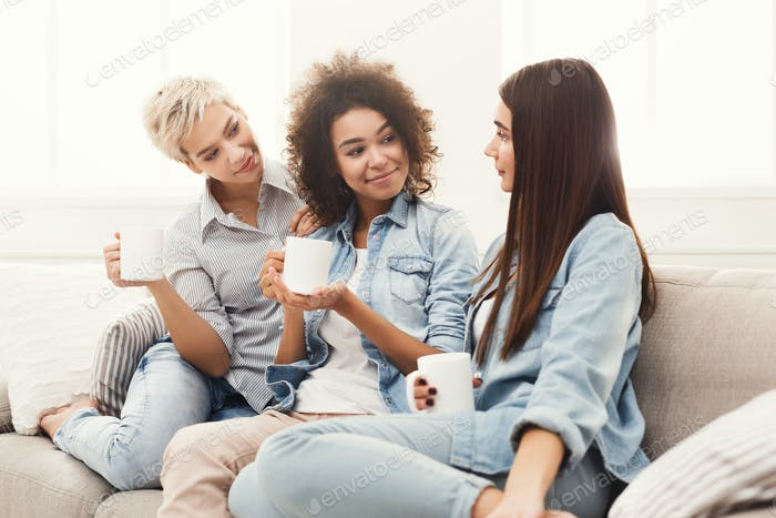 Three young female friends with coffee conversing