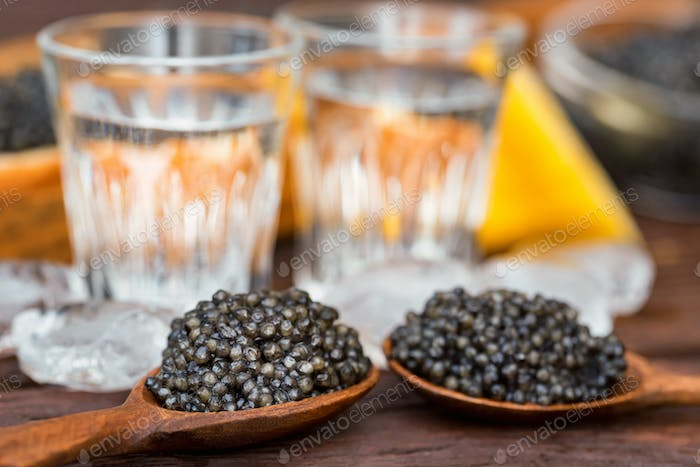Vodka and sandwiches with black sturgeon caviar close up