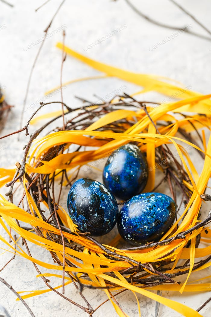 Easter Eggs in bird Nest. Quail easter eggs with feathers in nest on white table with copy space.