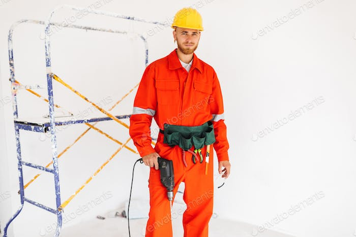 Young builder in orange work clothes and yellow hardhat looking