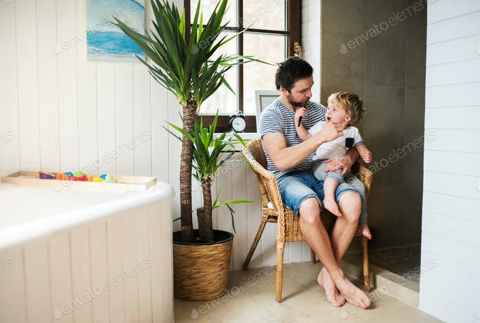 Father and a toddler boy sitting on a chair and brushing their teeth at home.