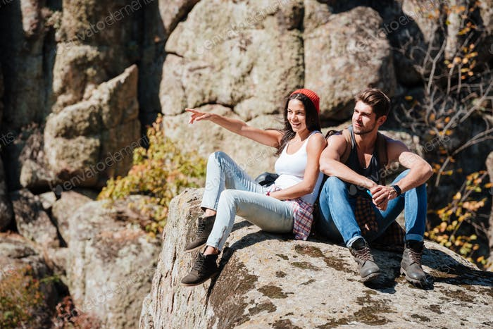Couple taking a break after hiking uphill and pointing finger