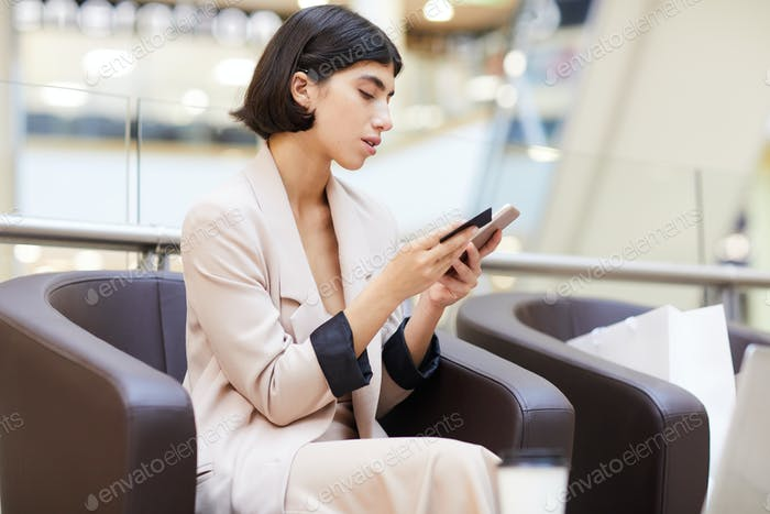 Beautiful Woman Using Mobile App in Mall