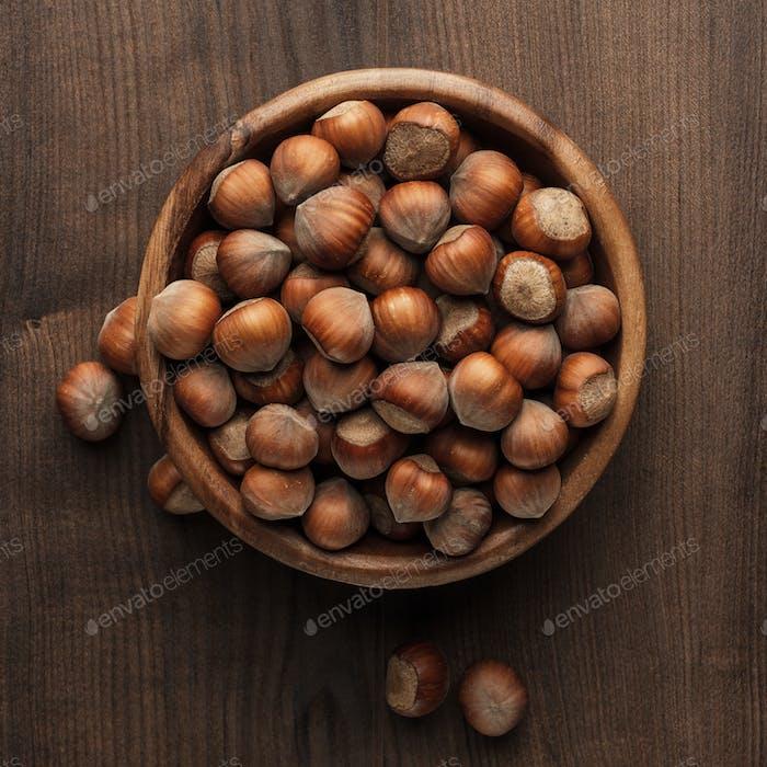 Avellanas en cuenco De madera en la mesa marrón