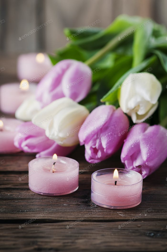 Pink and white tulips and candles on the wooden table