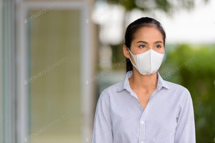 Mujer asiática con máscara facial para proteger del coronavirus Covid-19 mientras piensa