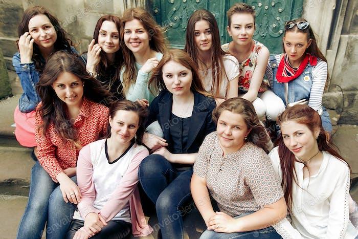 junge glückliche Frauen sitzen auf einer Treppe posieren