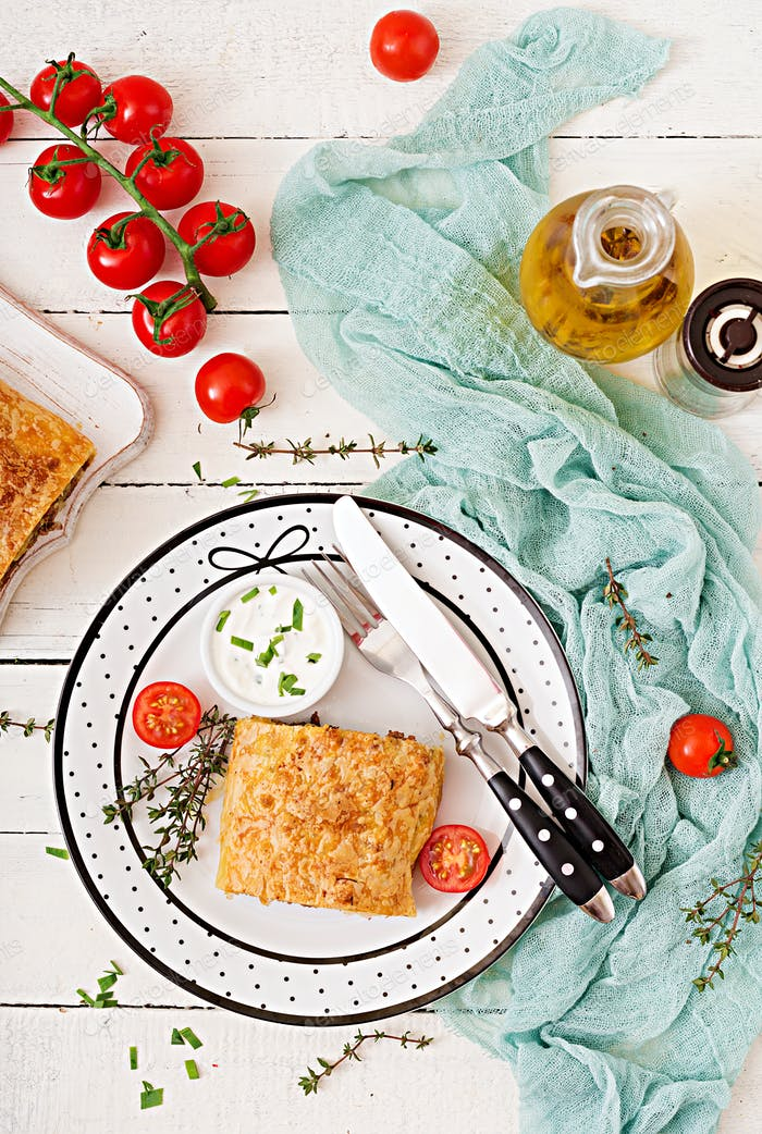 Appetizing strudel with minced beef, onions and herbs. Flat lay. Top view
