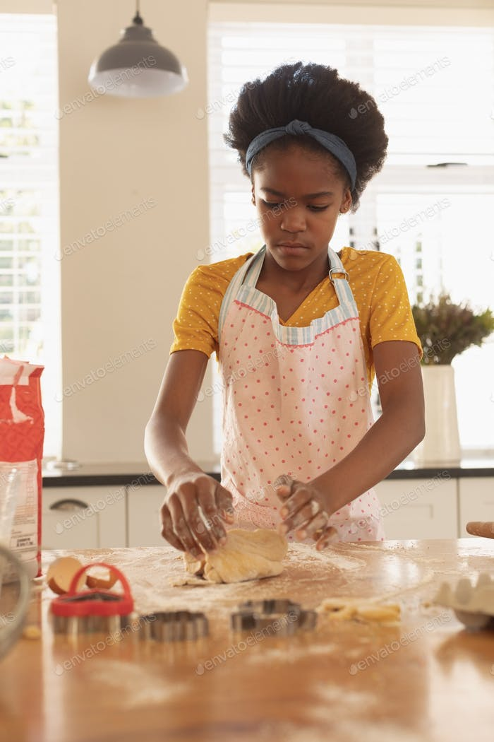 Front view of African American girl baking cookies in kitchen at home
