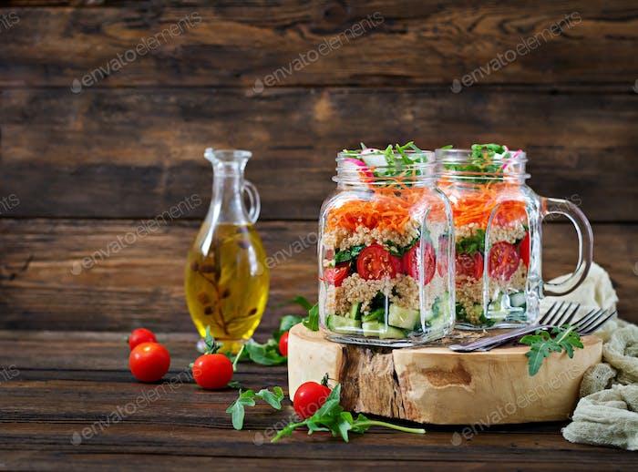 Salads with quinoa,  arugula, radish, tomatoes and cucumber in glass  jars