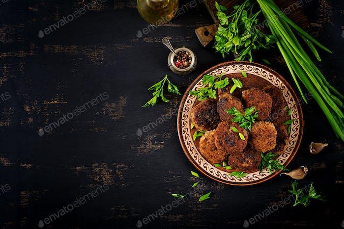 Saftige leckere Fleischkoteletts auf einem dunklen Tisch. Russische Küche. Ansicht von oben