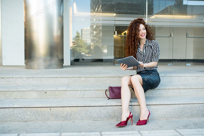 Young redhead business woman sitting on the stairs with tablet