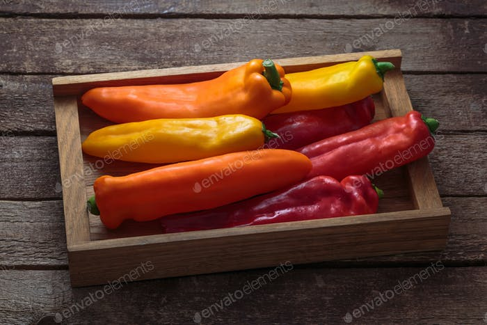 Box of ripe color peppers on wooden background