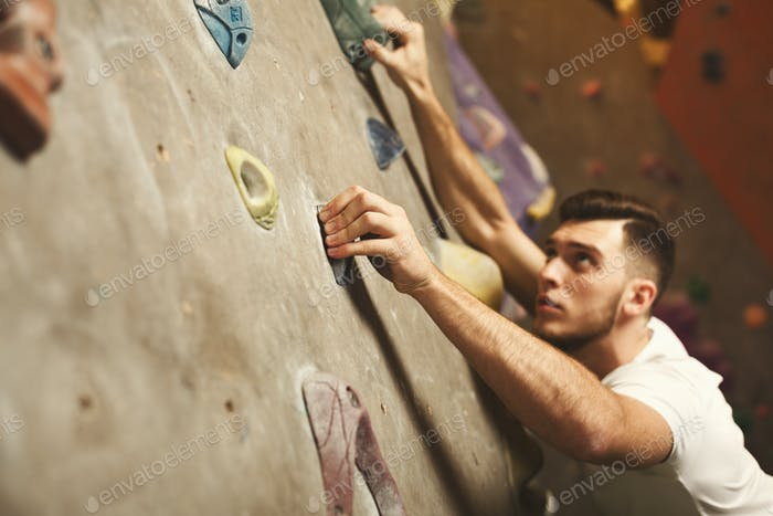 Thumbnail for Young man climbing artificial rock wall at gym