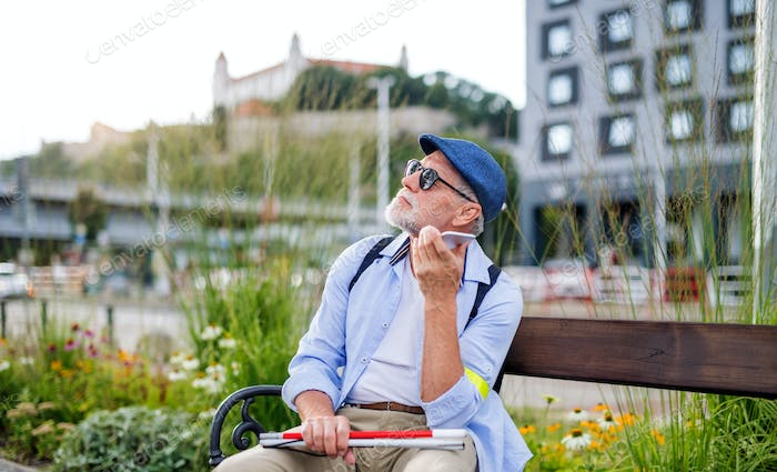 Senior blind man with smartphone sitting on bench in park in city