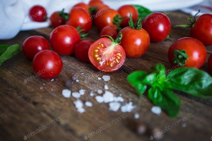 Fresh grape tomatoes with basil and coarse salt for use as cooking ingredients