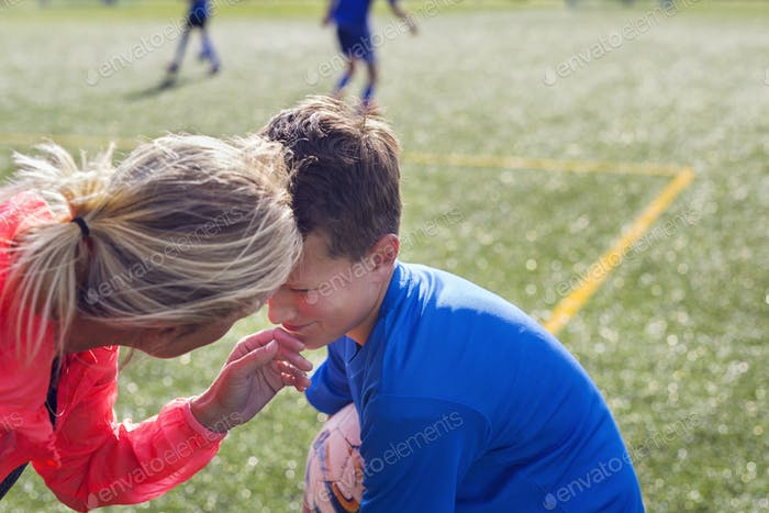 Mother comforting son (12-13) during soccer practice