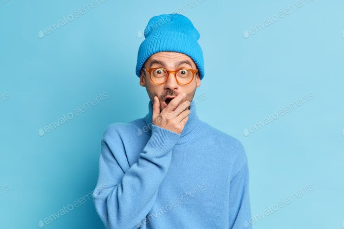 Shocked surprised man covers mouth and gazes at camera with stupefied expression hears unbelievable