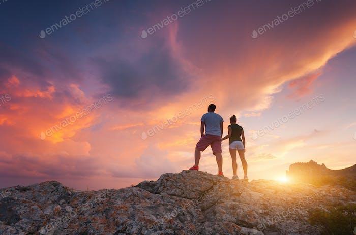 Silhouette glücklicher Menschen auf dem Berg gegen bunten Himmel