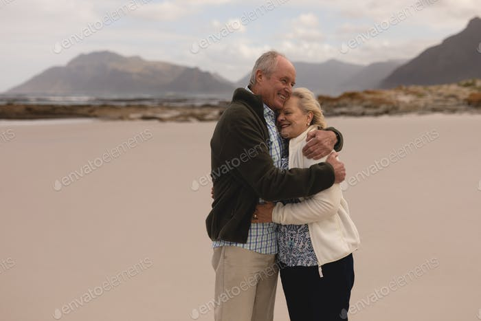 Happy senior couple embracing each other at the beach with mountains in the background