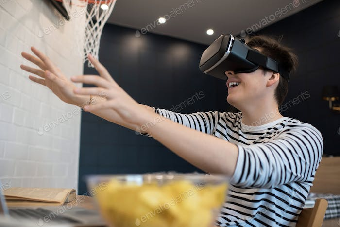 Young man sitting in VR glasses stretching arms