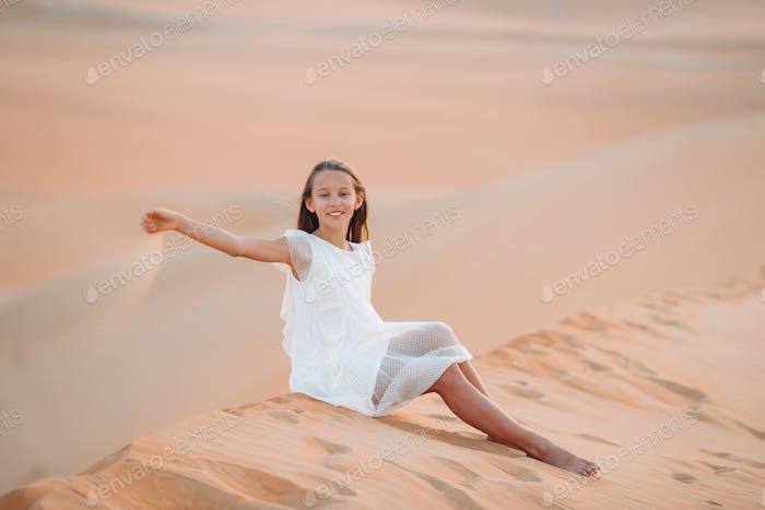 Girl among dunes in Rub al-Khali desert in United Arab Emirates