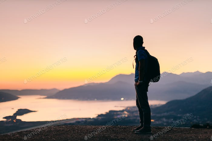 man travel mountains with sea view at sunset
