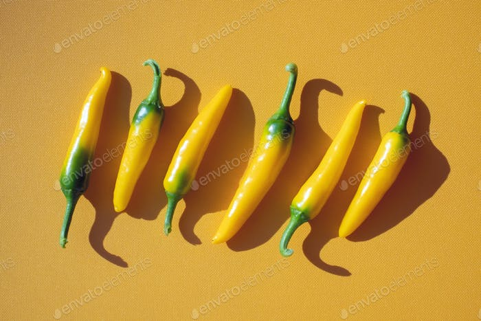 Yellow hot peppers on yellow background