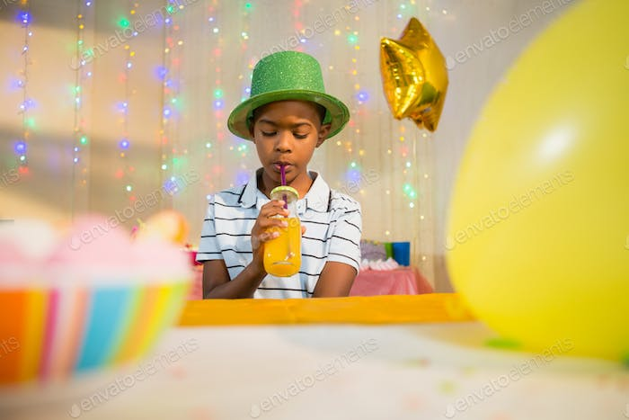 Boy drinking juice during birthday party
