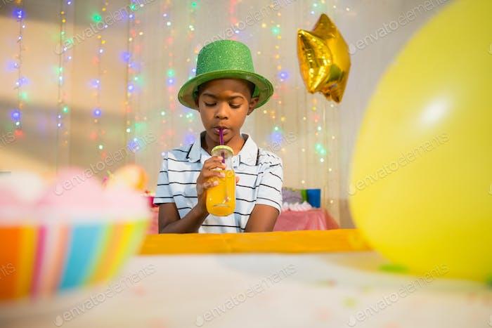 Junge trinken Saft während der Geburtstagsparty