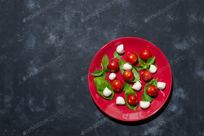 Italian caprese salad with sliced tomatoes, mozzarella cheese, basil, olive oil