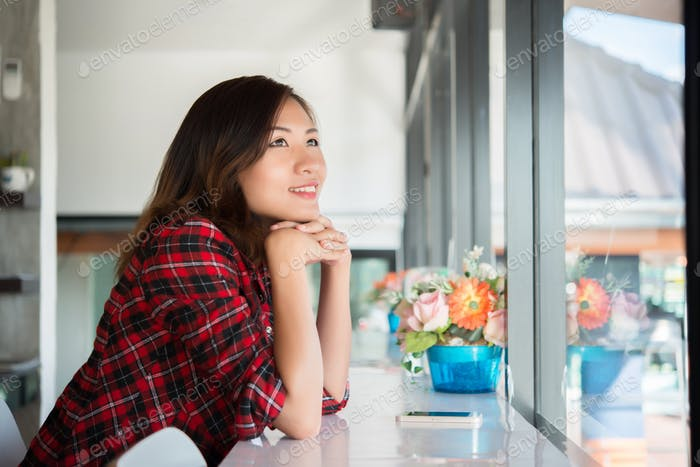 Beautiful asian woman sitting in the cafe , feeling happy and smiley face.