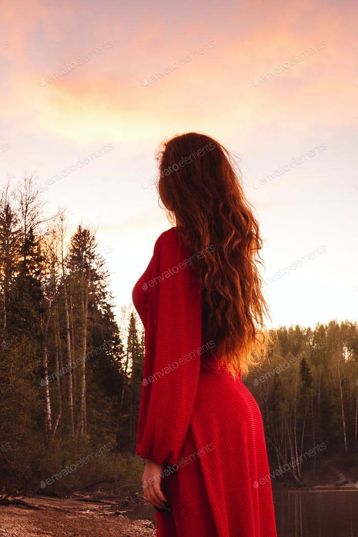 Young woman in red dress at sunset.