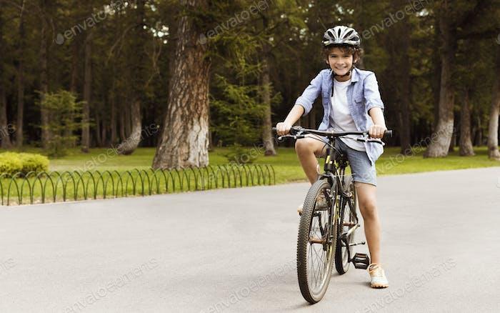 Niño de pie en una bicicleta en el parque público