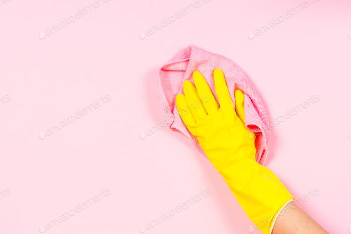 Hand in yellow gloves and microfiber rag cleaning pink background
