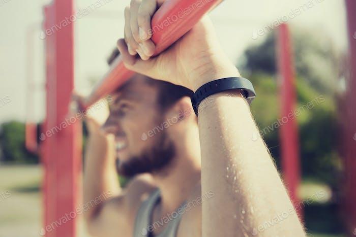 junger Mann Ausübung auf horizontalen Balken im freien