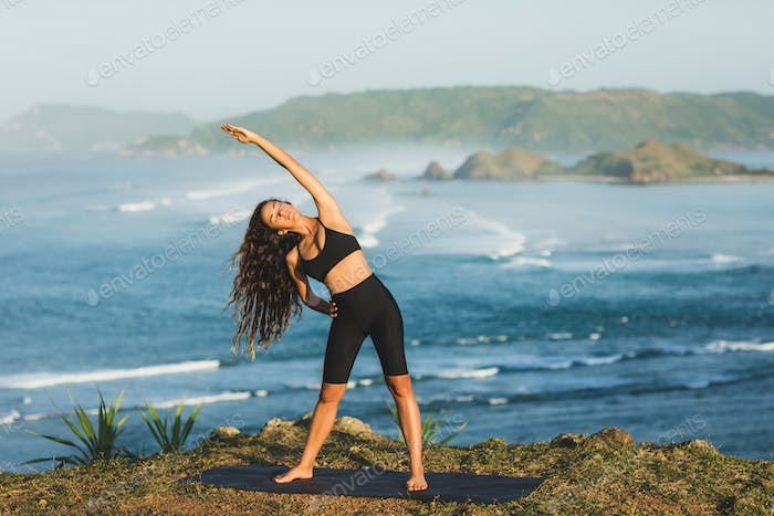 Young athletic sportswoman stretching and preparing for outdoors yoga workout